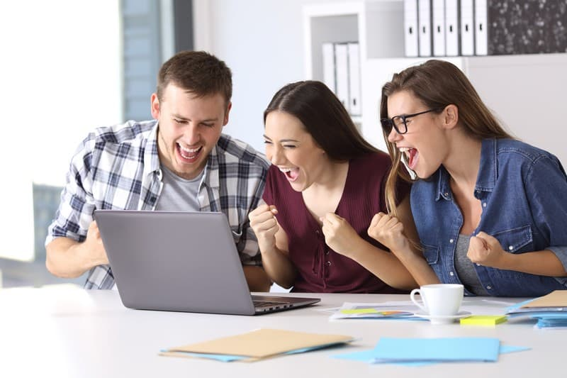 young employees around laptop